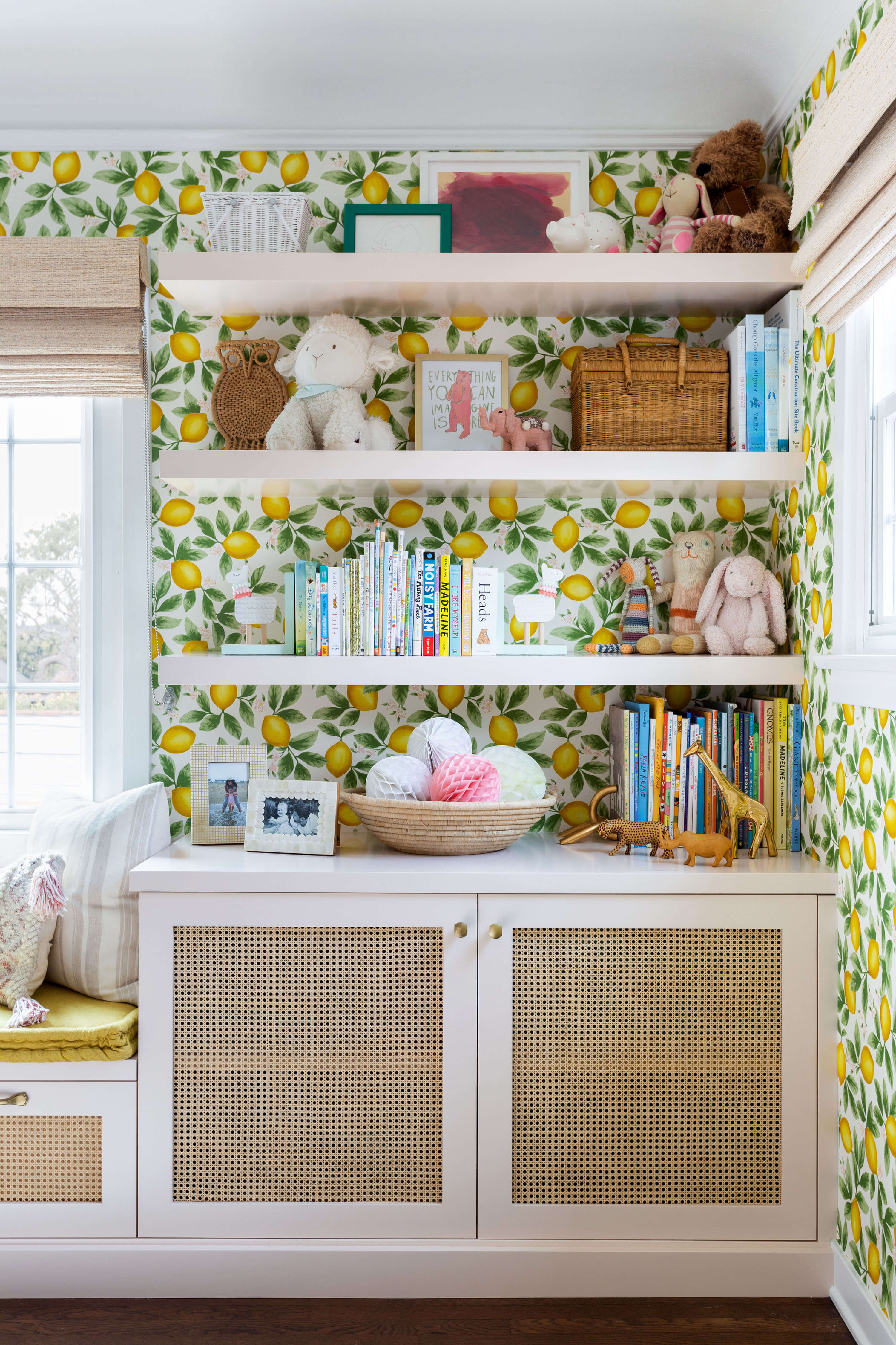 Ginny Macdonald and Lulu & Georgia girl's bedroom with lemon wallpaper and pink built in bookcase with cane cabinets