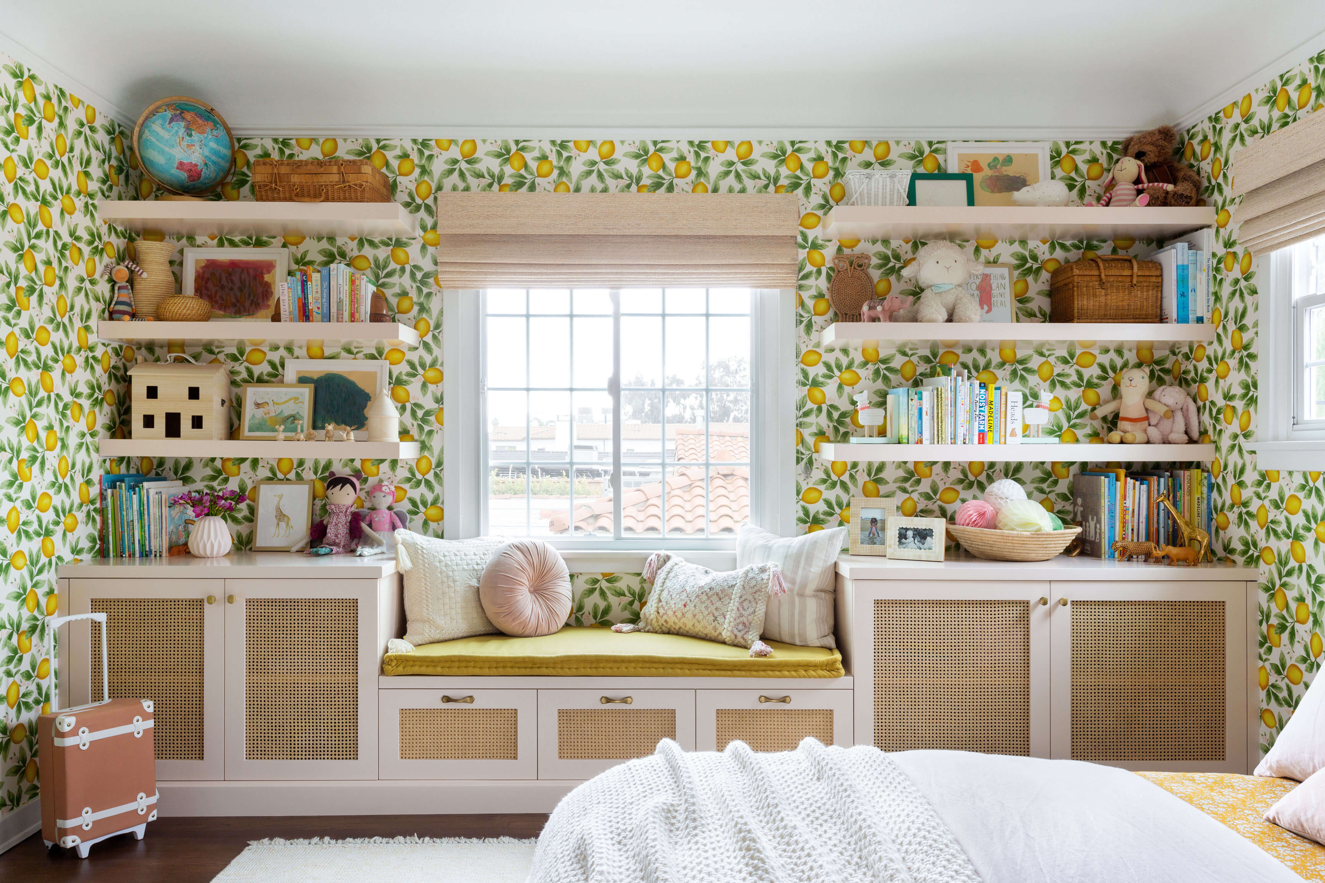 Ginny Macdonald and Lulu & Georgia girl's bedroom with lemon wallpaper and pink built in bookcase and bench with cane cabinets