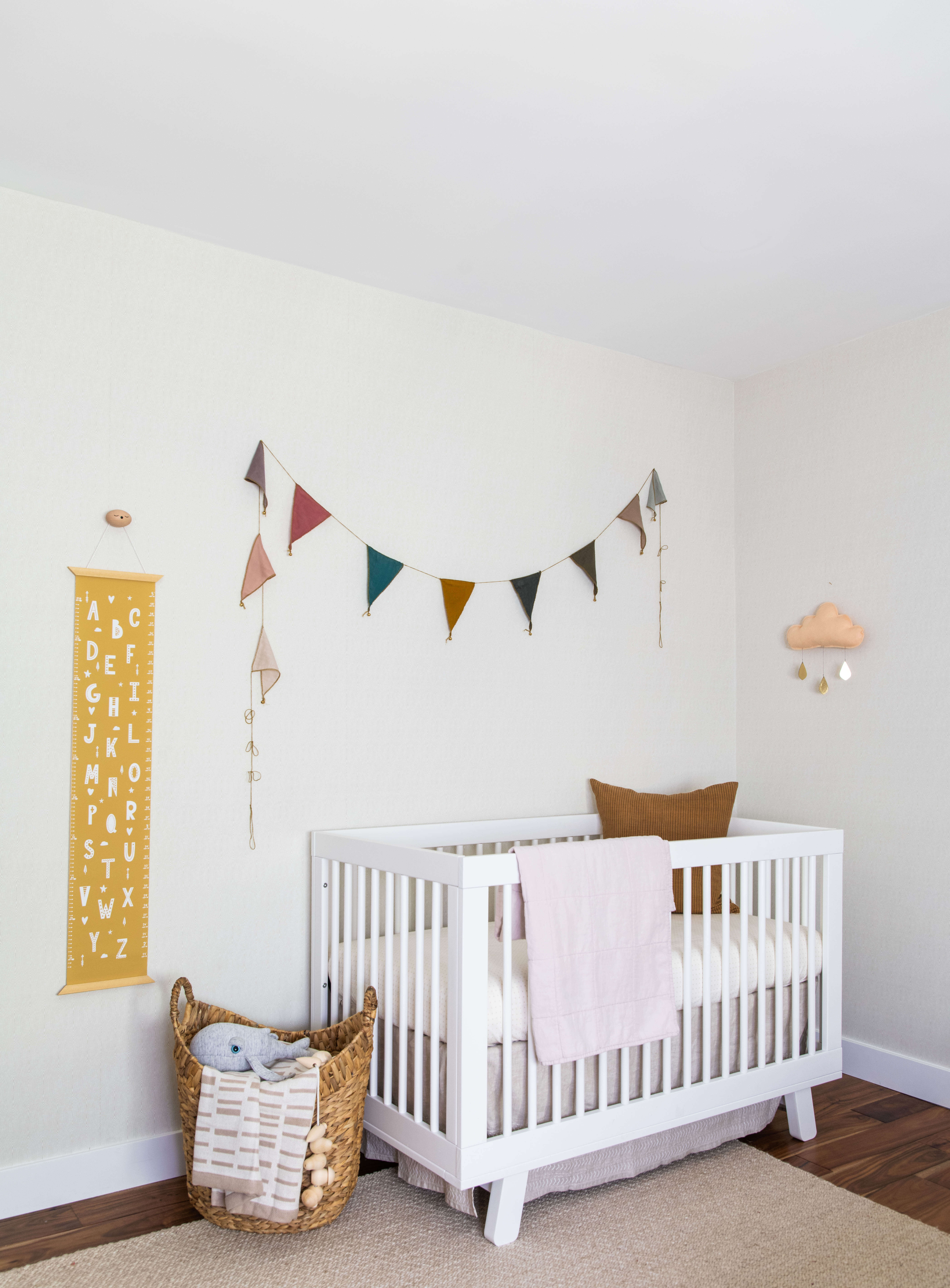 Ginny Macdonald Design nursery with multi coloured bunting and yellow height chart